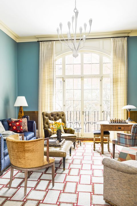 blue living room with a geometric rug and white pendant