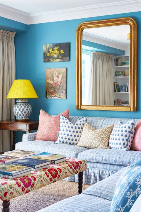 blue living room with large gilt mirror and yellow lampshade