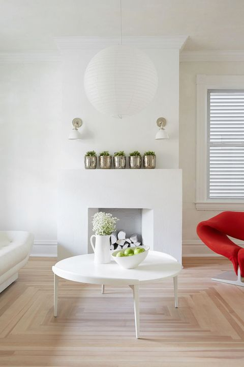 white living room with paper pendant light and red chair